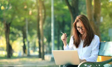 gente exitosa: Hermosa mujer de negocios soñando mientras se trabaja en el ordenador en su parque.