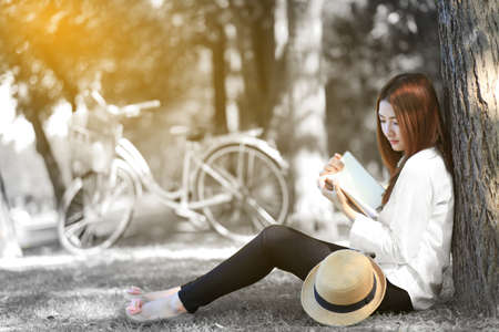 girl reading a book in autumn park. Banque d'images
