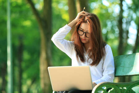net book: beautiful asian woman using laptop computer in the park