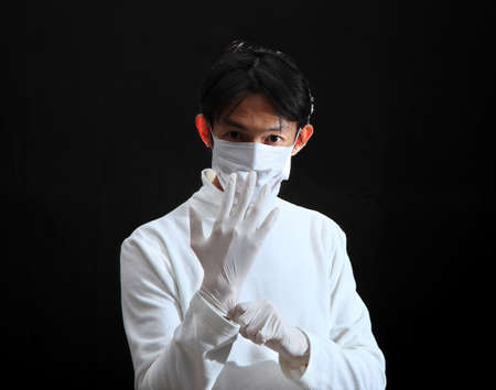 latex glove: Doctor putting on a latex glove. Stock Photo