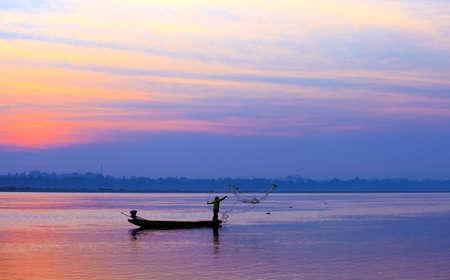 throwing fishing net during sunrise, Thailand