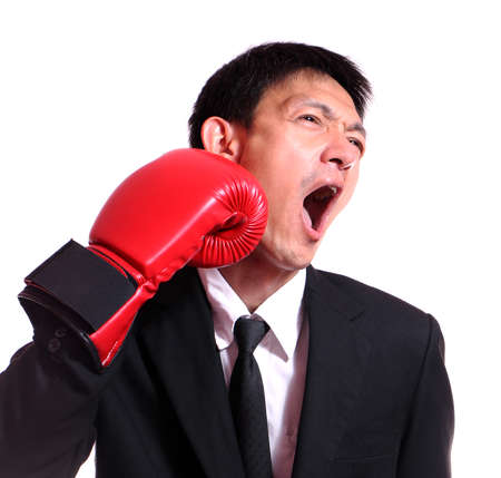 pangs: Business man hitting himself with a red boxing glove in the face