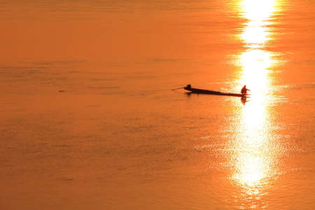 fishmonger in his traditional boat at sunrise photo
