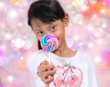 Beautiful little girl with lollipop on bokeh background. photo
