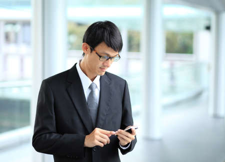 outdoorsman: Man on smart phone - young business man. Casual urban professional businessman using smartphone smiling happy outside office building. Handsome man wearing suit outdoors. Man on smart phone - young business man. Casual urban professional businessman using