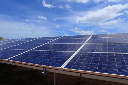 Sonnenkollektoren im Gras gegen sonnigen Himmel. Sonnenkollektoren im Kraftwerk für erneuerbare Energien Standard-Bild