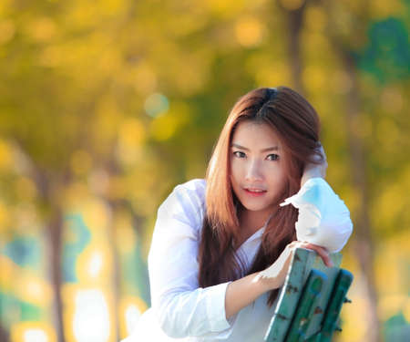 Woman smiling with perfect smile and white teeth in a park and looking at camera
