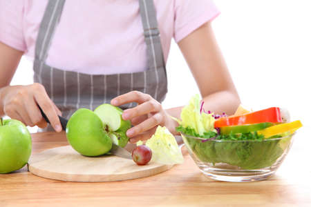 Asian girl was carrying a knife, cut the apple to salad vegetables and fruit.