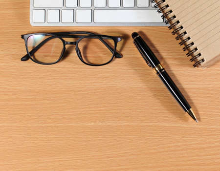 laptop and glasses, pen and notebook on wooden table,