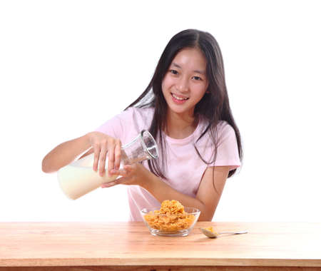 cereals holding hands: Cute girl having breakfast cereals with milk in the kitchen Stock Photo
