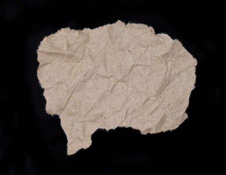 oude krant: close-up van een bruin gescheurd stuk krant op op een zwarte achtergrond