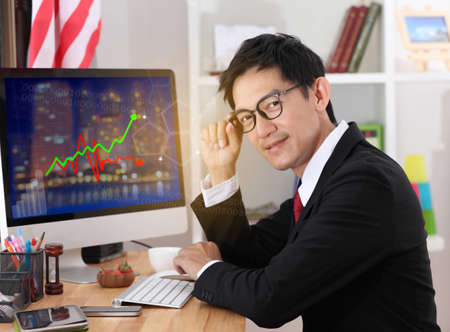 use computer: Business man use computer in office.Business man wearing glasses and smiling.business man working on computer. Stock Photo