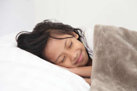 nine year old: Asian girl sleeping in bed. Nine year old girl a sleep with his head on a pillow and his cheek resting on his hands.
