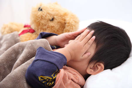 covering face: Sleeping child hands off covering face.