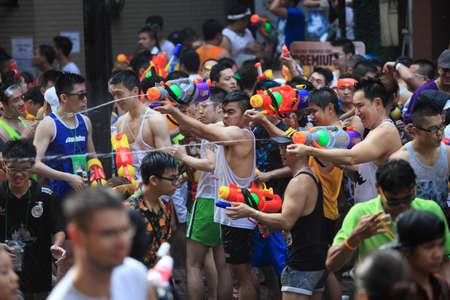 Bangkok, Thailand - April 13: Tourists shooting water guns and having fun at Songkran festival, the traditional Thai New Year, on Silom Road in Bangkok, Thailand.
