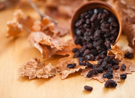 Black raisins in a wooden bowl. On dry leaf and brown wooden background.