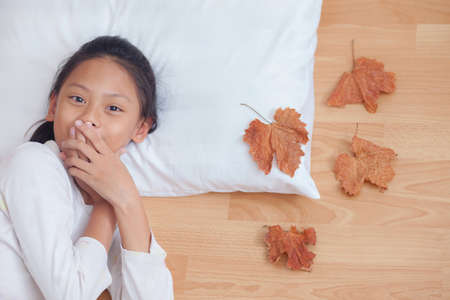 surprised girl screaming covering mouth her hands.In morning with brown dry leaf on the wooden floor.