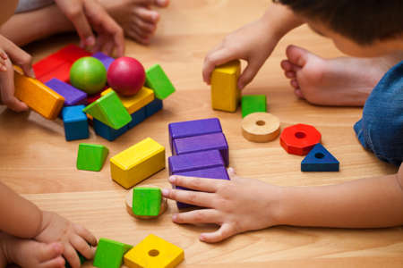 young children playing with wooden blocks in the room. 版權商用圖片