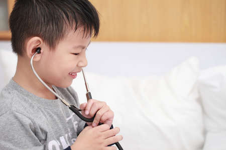 child playing doctor or nurse on the bedroom at home. Happy child listens a stethoscope to toy. Playful child take care.