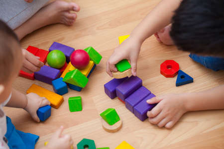 Three young children playing with wooden blocks in the room.