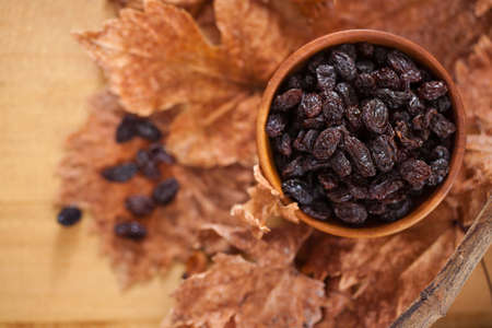 Black raisins in a wooden bowl. On dry leaves and brown wooden background. 版權商用圖片