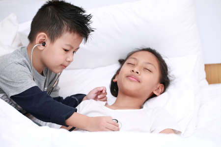 child playing doctor or nurse with plush girl with bright on the bedroom at home. Happy child listens a stethoscope to toy. Playful child take care my sister.