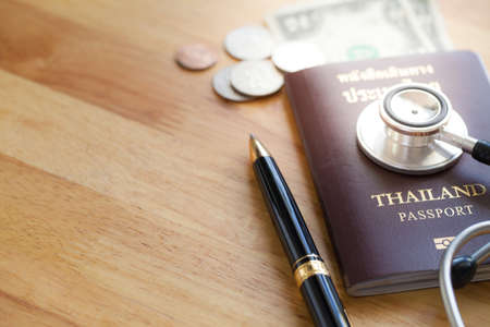 Medical tourism concept. Stethoscope with passport money and pen on wooden table.