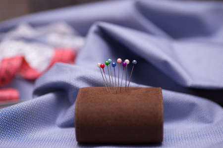 pincushion with pins on blue background