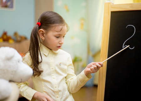 exacting: Little teacher. Beautiful young girl is teaching toys at home on blackboard. Preschool home education.