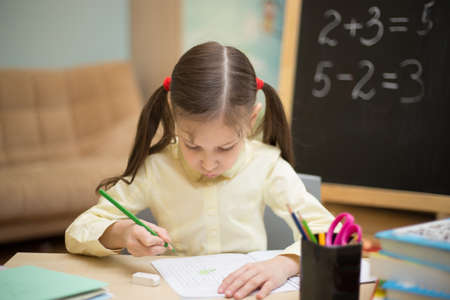 exacting: Little teacher. Beautiful young girl is teaching at home on blackboard. Preschool home education. Stock Photo