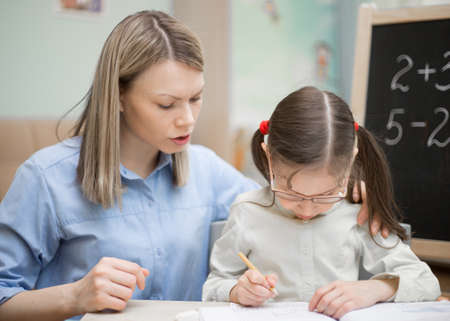 exacting: Preschool home education.  Beautiful young girl is teaching at home with lovely mother. Pretty young student. Stock Photo