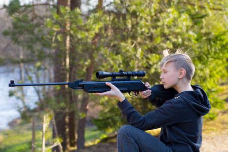 tiener met luchtgeweer in het bos Stockfoto
