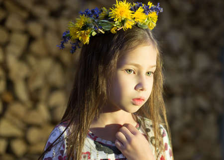 thicket: Young pretty girl in flowers wreath is staying near the woodpile  in the village. The beautiful witch.
