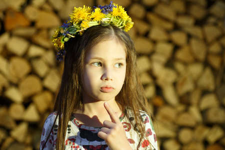 Young pretty girl in flowers wreath is staying near the woodpile  in the village. The beautiful witch.