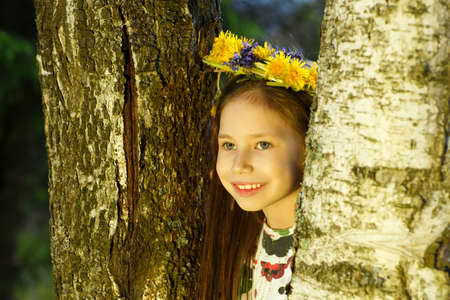 Cute girl in flowers wreath is looking out of birch tree in forest. The young witch. Stock Photo