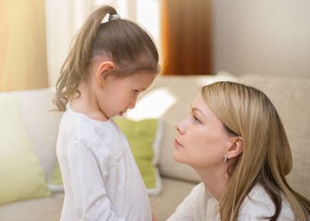 Schöne Mutter tröstet ihre traurige kleine Tochter zu Hause. Familienbeziehungen. Standard-Bild - 82278033
