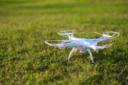 Drone quad copter with high resolution digital camera landing on green grass.