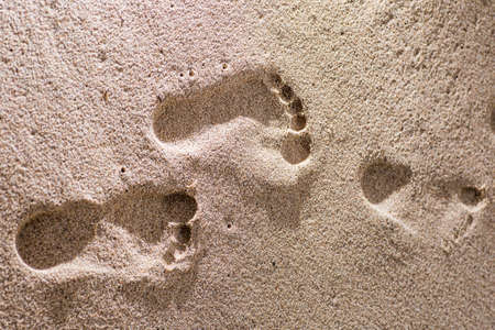 Human footprints on the sand beach. Travel vacations concept. Stock Photo