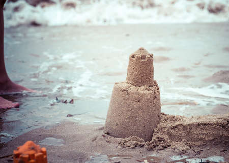 Persistent tower of the sand castle washes away in the sea water. Reklamní fotografie - 95911568
