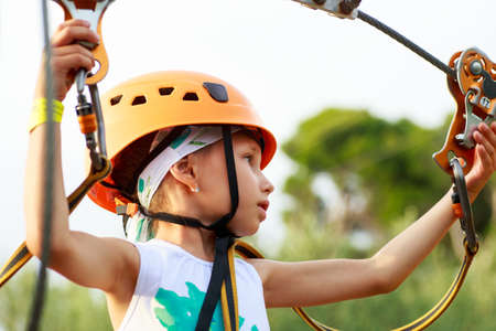 Cute  girl enjoying a sunny day in a climbing adventure activity park.  girlat climbing activity in high wire forest park.