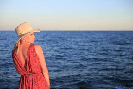 Young woman, wearing white hat and red dress, enjoying sea view. Stock Photo