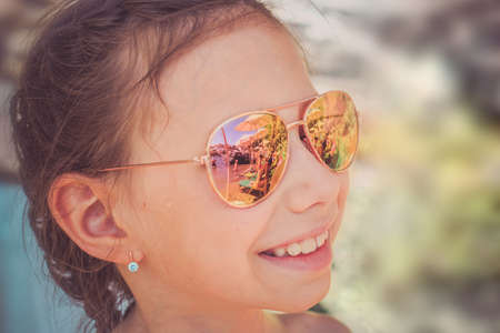 Beautiful young girl in sunglasses with beach reflection. Holidays, travel, vacation and happiness concept.