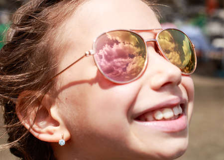 Beautiful young girl in sunglasses with sky rerlection. rerlection Holidays, travel, vacation and happiness concept.