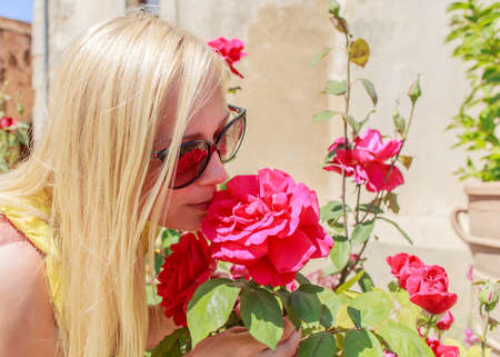 Beautiful woman sniffs fragrant red roses in the garden.