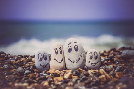 Group of stones with drawn faces in the sand. Father, mother, daughter and son. Concept of happy family