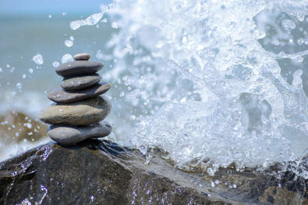 Balance zen stones pyramid on pebble beach with a splashing wave. Stability, balance, and harmony concept. 版權商用圖片