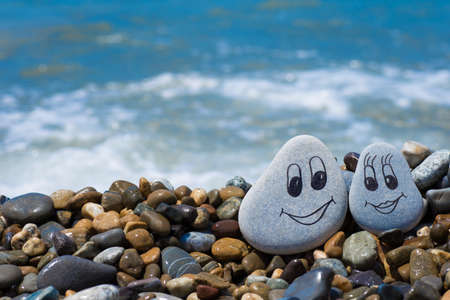 Pebbles with drawn faces in the sand. Loving couple. Travel concept 版權商用圖片