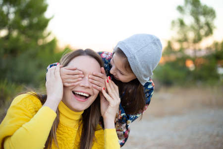 Happy young girl laughing, covering eyes of her mother with her hand. Adorable little girl surprising her mother