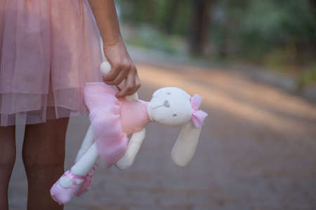 Soft toy rabbit in hands of girl walking in fall park.