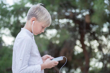 boy with headphones, phone and tablet walks in the city and park. 版權商用圖片